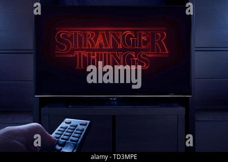 A man points a TV remote at the television which displays the Stranger Things main title screen (Editorial use only). - Stock Image