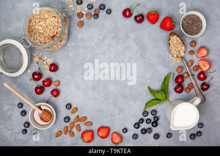 ingredients for breakfast: granola, chia seeds, fresh berries and nuts on a gray background. view from above. - Stock Image