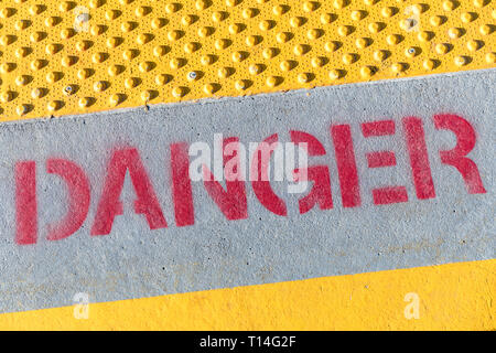 'Danger' sign, red stencil letters on concrete, yellow border with studded non-slip surface - Stock Image