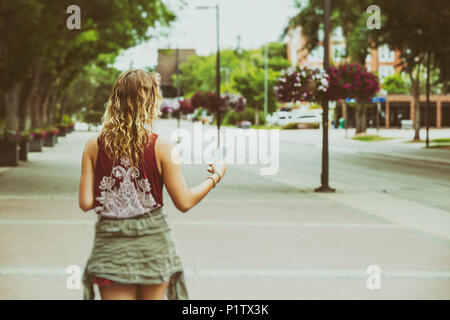 A young woman walks down a path on a university campus reading from her smart phone; Edmonton, Alberta, Canada - Stock Image