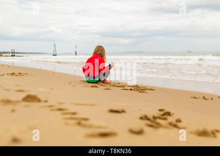 Young child sat on beachs waters edge lost in thought, taken from behind. Poole, Dorset, England. - Stock Image