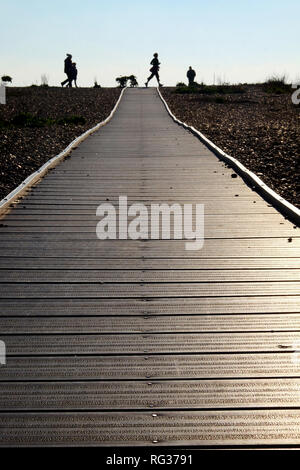 Looking down a long straight wooden pathway with a pebble beach on both sides at the end are unrecognizable people walking and jogging silhouetted by  - Stock Image