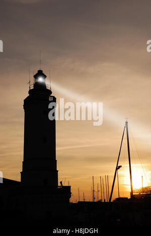 lighthouse at sunset on the port with cloudy sky - Stock Image