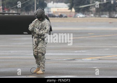 A U.S. Army Soldier assigned to 2-158th Assault Helicopter Battalion, 16th Combat Aviation Brigade, 7th Infantry Division prepares a UH-60 Black Hawk to depart from Joint Base Lewis-McChord, Wash., for the National Training Center Jan. 9, 2016. The Soldiers and aircraft will participate in training with other units from 7th Infantry Division to prepare for future missions. (U.S. Army photo by Capt. Brian Harris/Released) - Stock Image