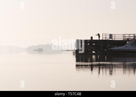 Luss, Loch Lomond, Scotland, UK. 22nd Apr, 2019. uk weather - a fisherman takes advantage of a glorious still and hazy quiet morning at Luss, Loch Lomond Credit: Kay Roxby/Alamy Live News - Stock Image