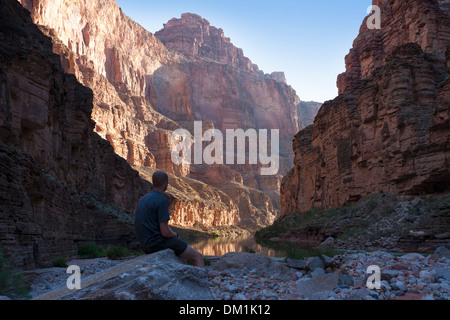 A man watches the sunrise in the Grand Canyon, Arizona, USA. - Stock Image