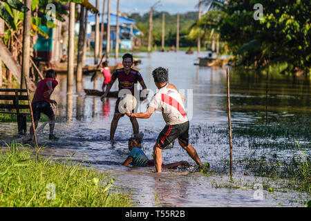 Locals playing soccer on a flooded street - Stock Image