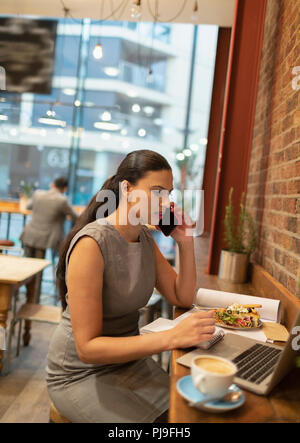 Businesswoman talking on smart phone, working at laptop in cafe - Stock Image