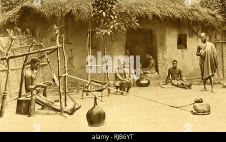 Weaving cloth with hands and feet in a village on the Gold Coast (then part of the British Empire), West Africa. - Stock Image