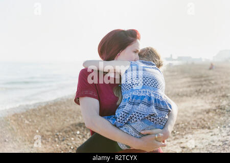 Affectionate mother holding daughter on sunny beach - Stock Image