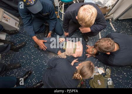 180825-N-HE318-1026 PHILIPPINE SEA (Aug. 25, 2018) Hospital Corpsman 2nd Class Devina Gutual, from Salinas, Calif., receives medical attention as a simulated casualty during a general quarters training exercise aboard the Ticonderoga-class guided-missile cruiser USS Antietam (CG 54). Antietam is forward deployed to the U.S. 7th Fleet area of operations in support of security and stability in the Indo-Pacific region. (U.S. Navy photo by Mass Communication Specialist 2nd Class William McCann/Released) - Stock Image
