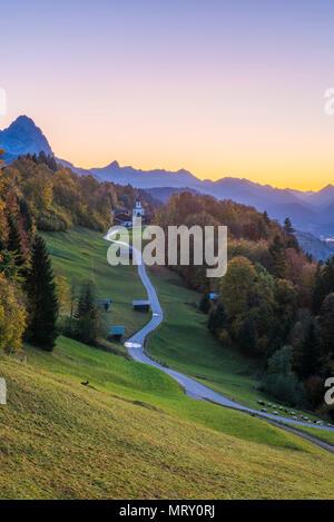 Wamberg, Garmisch Partenkirchen, Bavaria, Germany, Europe. Wamberg village at dusk. Garmisch Partenkirchen and Zugspitze mountain in the background - Stock Image