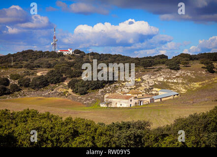 A communications mast towers above a spreading, but deserted farmhouse or casa de Campo, with tilled fields in front. Province of Granada, Spain - Stock Image