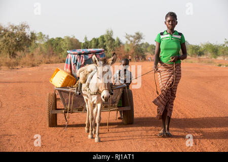 Samba village, Yako Province, Burkina Faso: Abzetta Sondo, 19, returns with full water  container from the well for her household. - Stock Image