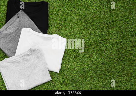 Stack of arranged different coloured mens T-shirt on grass background. Horizontal view. - Stock Image