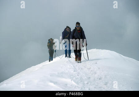 Three climbers approaching the summit of the Breithorn in the Swiss Alps - Stock Image