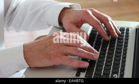 Close shot of male hands typing on a laptop keypad. - Stock Image