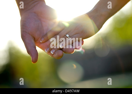 Closeup photo of an engaged couple holding hands showing engagement ring. - Stock Image