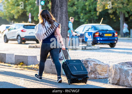 Strasbourg, Alsace, France, rear view of a young woman pulling her roller suitcase on pavement, - Stock Image