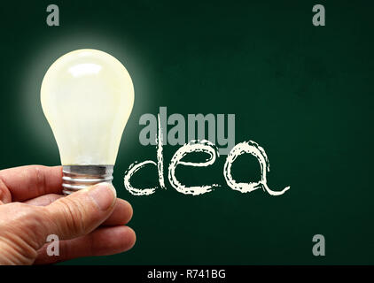 Man holding illuminated bulb with bare hands against chalkboard with the word Idea. Concept of bright idea, innovation, imagination, inspiration, visi - Stock Image