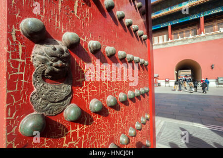 Lion design on a red wooden door leading to the northern gate of the complex, the Gate of Divine Might - Stock Image