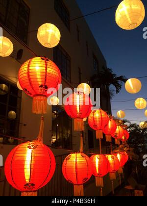 Paper lanterns glow at dusk over restaurant patio in Miami, Florida. - Stock Image