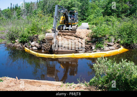 A track hoe machine with an operator building a new logging bridge over the Kunjamuk River in the Adirondack Mountains, NY USA - Stock Image