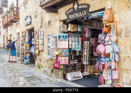 Santillana, Spain - 8th July 2018: Tourists looking at souvenirs outside a shop. Many tourists visit the town. - Stock Image