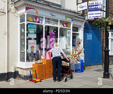 Customers outside Age Concern charity shop, England UK - Stock Image