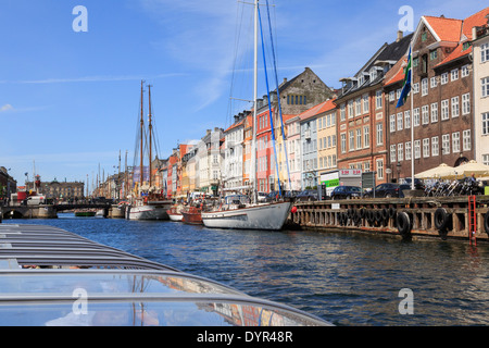 Tourists canal sightseeing tour boat passing old buildings on quay at Nyhavn, Copenhagen, Zealand, Denmark, Europe - Stock Image