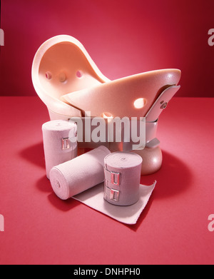 Emergency medical supplies; neck brace, gauze and bandages. Bright red background. - Stock Image