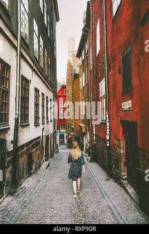 Woman walking in Stockholm traveling  lifestyle summer vacations in Sweden old city cobblestone street - Stock Image