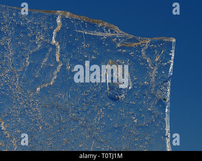 Sun rays caught in cracks in ice piece. Broken floe turn against to sharp sun. - Stock Image