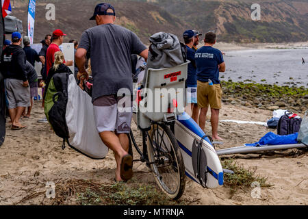 Man with a surfboard attached to a bicycle at a beach in California - Stock Image