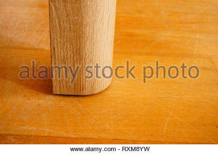 Wooden table foot close up on a parquet floor. - Stock Image