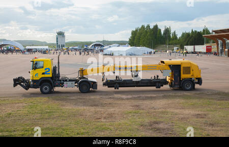 Vammas SB 4500 tow-behind sweeper clears the runway of foreign objects and snow in wintertime in Jyväskylä Airport at Tikkakoski, Finland. - Stock Image