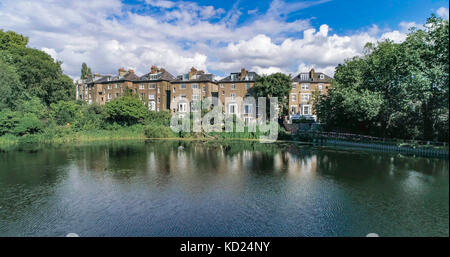 Aerial view of Victorian houses reflecting on a pond in a park in North London - Stock Image