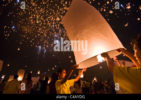 Thailand, Chiang Mai, San Sai.  Revellers launch khom loi (sky lanterns) into the night sky during the Yi Peng festival. - Stock Image