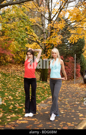 Portrait of two young women stretching their arms during autumn - Stock Image