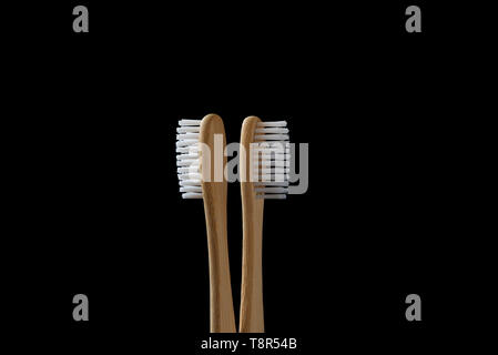 Pair of Bamboo tooth brushes on a black background. Eco friendly hygiene product. - Stock Image