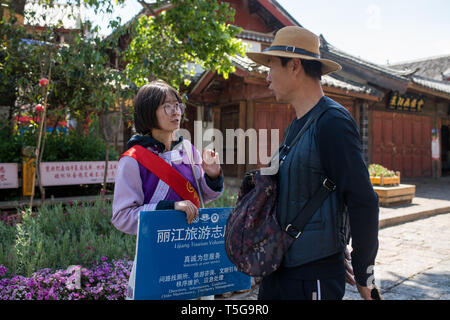 Lijiang, China's Yunnan Province. 22nd Apr, 2019. A volunteer helps a tourist in Lijiang, southwest China's Yunnan Province, April 22, 2019. According to local authority, tourism started to heat up when a faster train service was launched between Lijiang and provincial capital Kunming in early 2019. During the first season, Lijiang welcomed 12.325 million arrivals and saw a total revenue of 25.637 billion yuan, up 21.5 percent and 15.13 percent respectively than the previous year. Credit: Hu Chao/Xinhua/Alamy Live News - Stock Image