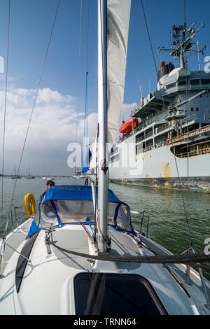 Sailing yacht going past a moored Royal Navy vessel moored in Portsmouth Harbour - Stock Image
