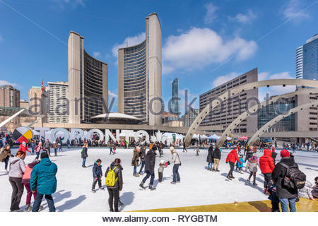 Toronto city hall in winter with peple skating rink and Toronto sign in Nathan Phillips Square in Toronto Ontario Canada - Stock Image
