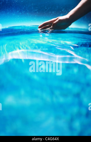 hand in blue water - Stock Image