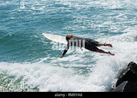 A man diving into the sea with a surfboard. - Stock Image