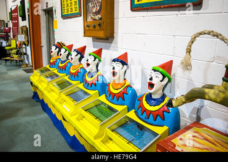 A vintage carnival game with a row of brightly painted clown heads for sale in an antique mall in Australia. - Stock Image