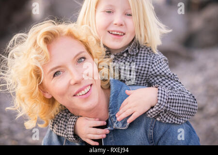 cheerful and happy couple mother and young children son having fun together - mom carry his little boy on her shoulder and both laugh and smile - brig - Stock Image