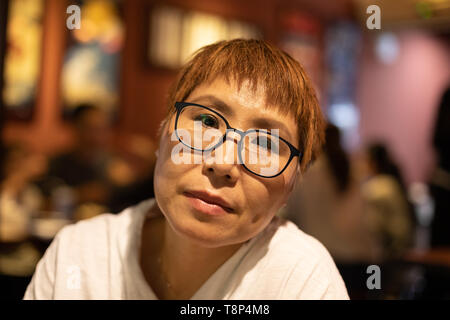 Mature Taiwanese woman of Chinese ethnicity sitting in a warm, cozy restaurant - Stock Image