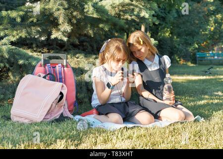 Two little schoolgirls using smartphone. Children playing, reading, looking at the phone. People, children, technology, friends and friendship concept - Stock Image