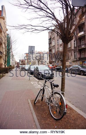 Poznan, Poland - March 8, 2019: Bicycle locked on a metal barrier next to tree on a sidewalk in the Slowackiego street in the city center. - Stock Image
